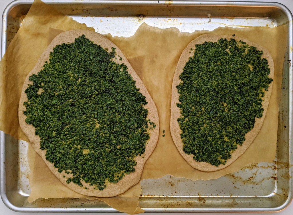 Baking tray with two zesty pizzas primed for the oven