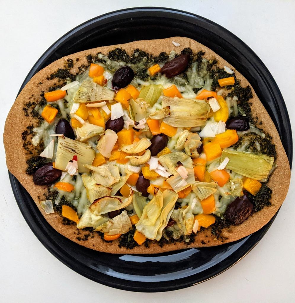 zesty pizza with basil pesto, artichokes, Kalamata olives, mozzarella cheese, peppers, garlic, and onions