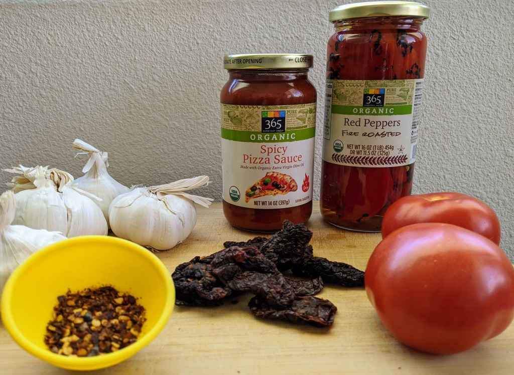 ingredients for the Il Diavolo pizza, garlic, tomatoes, sun dried tomatoes, red pepper flakes, red peppers, and spicy pizza sauce