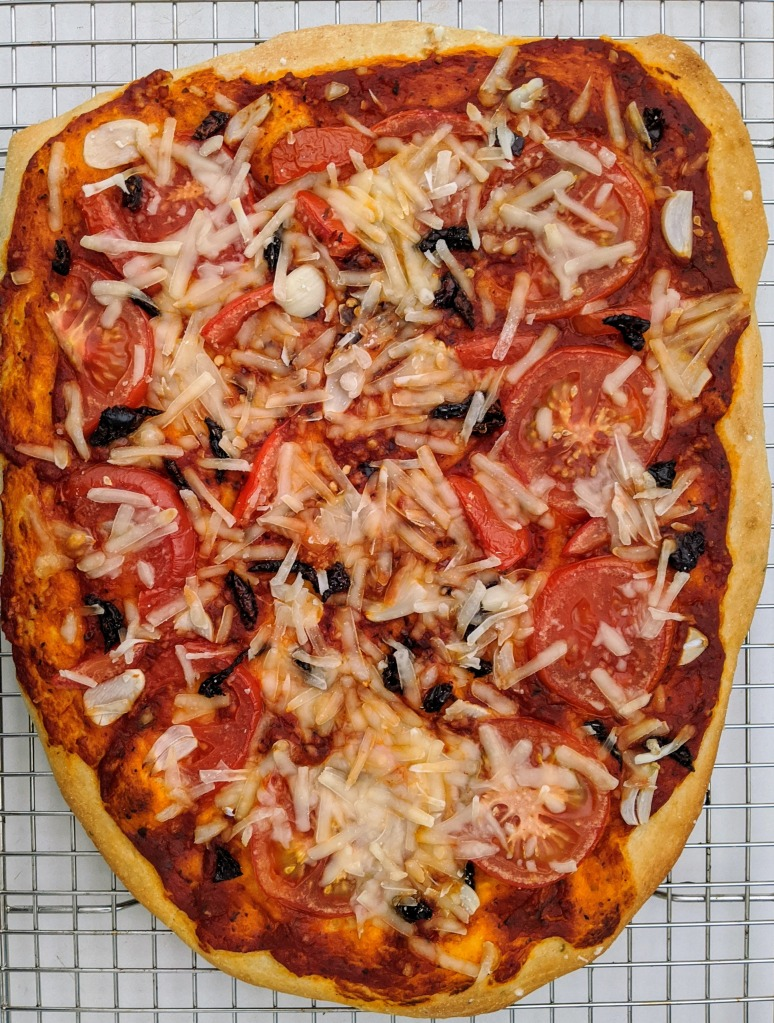Baked Il Diavolo pizza with garlic, tomatoes, vegan mozzarella, and spices